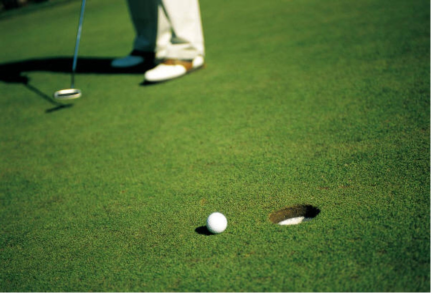 golfer on a putting green by a tee