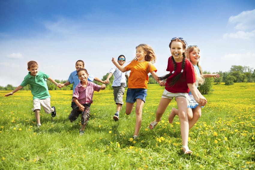 a group of neighborhood kids running through a field together