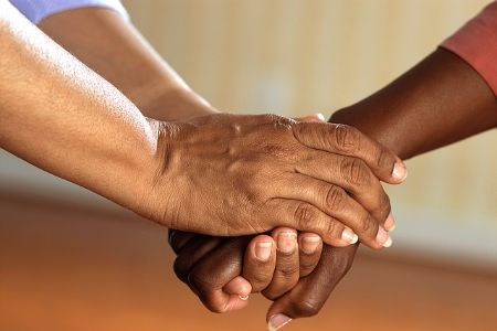 two residents clasping hands together in support
